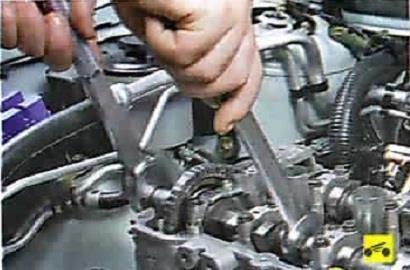 Снятие болта крепления шестерни привода выпускного вала Nissan Almera Classic