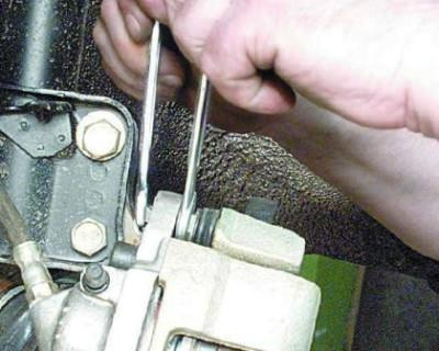 Используя два ключа открутите болт верхнего узла крепления суппорта тормоза.