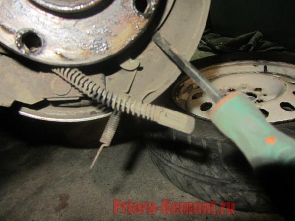 вытащить трос ручника из рычага привода на Приоре