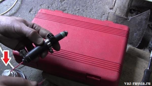 Стрелкой указано место на которое необходимо нажать, если форсунка стала очень плохо распылять жидкость находящуюся в баллоне