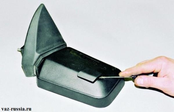 Поддевание отверткой небольшой заглушки квадратной формы бокового зеркала