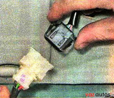 Сжав с двух сторон пружинные фиксаторы, разъединяем колодки жгута проводов
