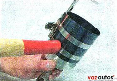 Надеваем оправку на поршень и обжимаем ею кольца, периодически слегка постукивая ручкой молотка по оправке для самоустановки колец