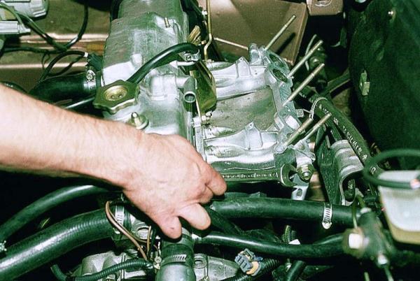 Откручивание гайки верхнего крепления левого кронштейна впускного коллектора 8-клапанного двигателя Лада Гранта (ВАЗ 2190)