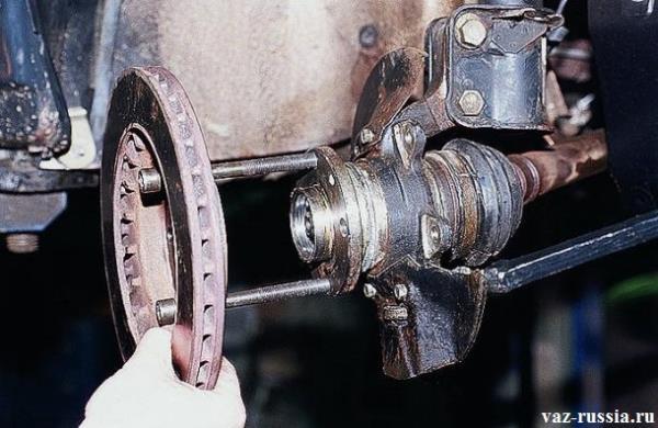 Продевание двух болтов через снятый ранее тормозной диск и заворачивание после этого их в саму ступицу и снятие самой ступицы вследствие этого