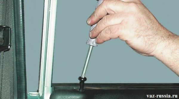 Отворачивание отвёрткой кнопки при помощи которой закрывается и открывается дверь у автомобиля