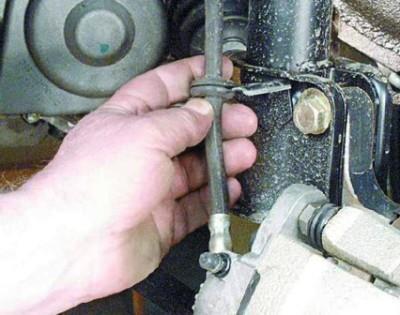 Извлеките из кронштейна крепежа шланг тормозной системы. В противном случае он затруднит вам процесс открытия тормозного суппорта.