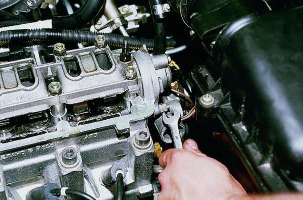 Откручивание гайки крепления заглушки головки блока цилиндров двигателя Лада Гранта (ВАЗ 2190)