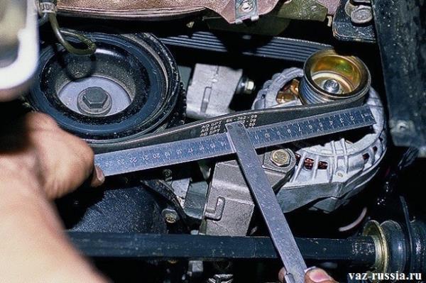 Проверка с помощью линейки натяжения ремня генератора