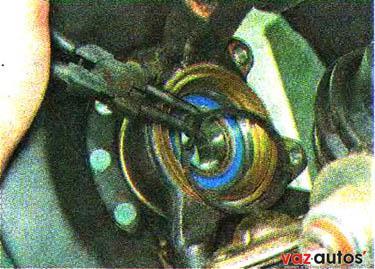С обратной стороны поворотного кулака съемником сжимаем и снимаем другое стопорное кольцо подшипника ступицы