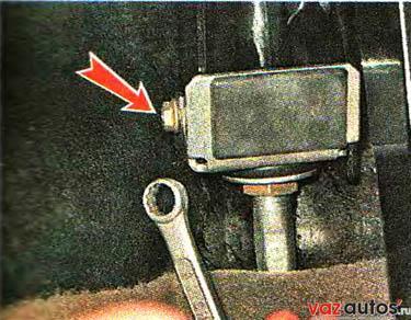 В салоне, под панелью приборов. ключом на 8 мм отворачиваем гайку крепления кронштейна оболочки троса к кронштейну педали сцепления