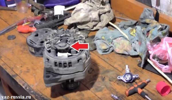 Стрелкой показано где на генераторе стоит регулятор напряжения, но при этом ещё и крышка с генератора снята, можно даже сказать что он частично разобран