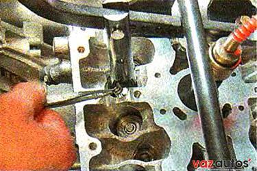 Удерживая пружину сжатой, пинцетом извлекаем два сухаря клапана