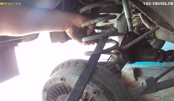 Поднимание задней пружины за нижний витки при помощи монтажной лопатки