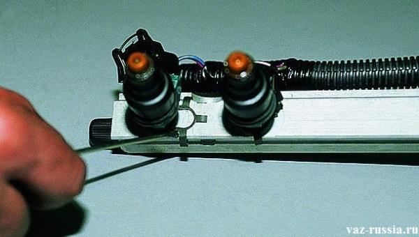 Смещение металлического фиксатора в сторону, за счет поддевания его отверткой