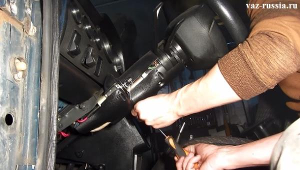 Отворачивание нижних винтов для снятия кожуха с рулевой колонки