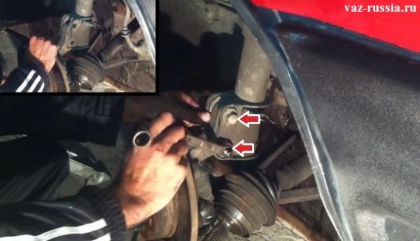 Удерживание болтов и отворачивание гаек их креплений и вследствие чего снятие поворотного кулака вместе с тормозным диском с автомобиля