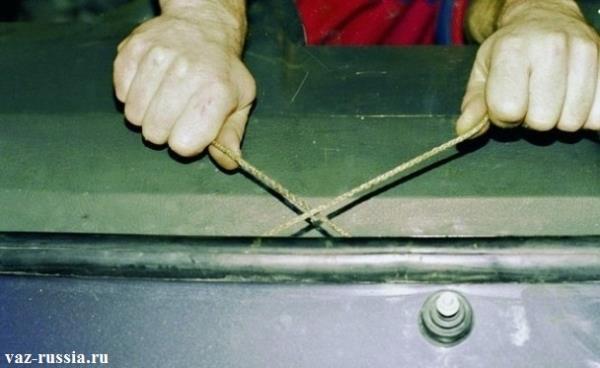 Аккуратное вытягивание на себя верёвки, и прижимание самого стекла помощником при этом
