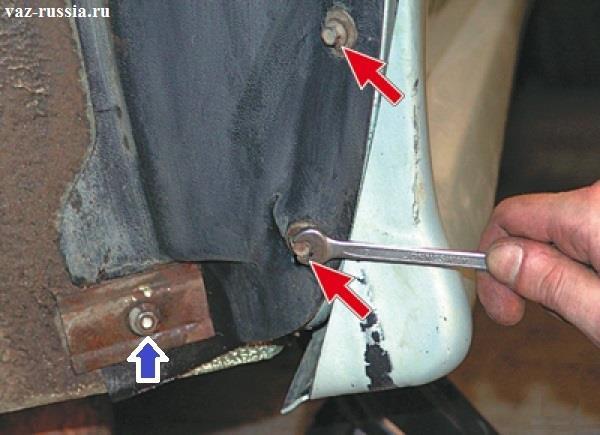 Отворачивание гаечным ключом болтов которые указаны красными стрелками и выворачивание гайки которая указана синей стрелкой и которая крепит прижимную пластину, которая в свою очередь крепит подкрылку к автомобилю