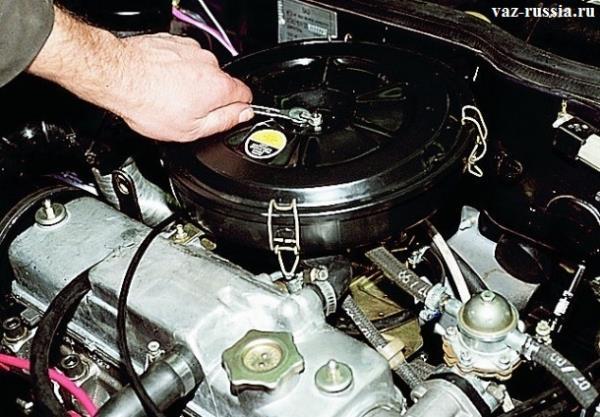 Отворачивание центральной гайки крепления крышки корпуса воздушного фильтра