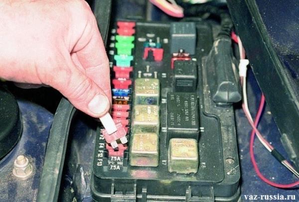 Извлечение предохранителя из монтажного блока автомобиля при помощи специальных маленьких щипцов