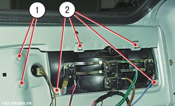 На фото изображены гайки которые крепят задний фонарь и фонарь освещения номерного знака к машине