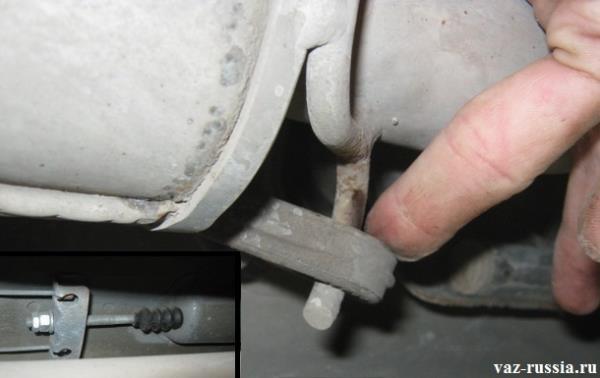 Выведение из проушины глушителя в передней его части подушки, которая его удерживает, для того чтобы металлический кожух можно было продвинуть в переднюю часть автомобиля