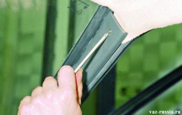 Отворачивание верхнего винта крепления боковой накладки