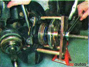 Упираем лапы съемника в поворотный кулак и, вращая гайку болта, выпрессовываем ступицу из поворотного кулака