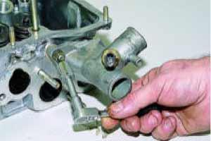 Головкой «на 13» отворачиваем две гайки крепления отводящего патрубка рубашки системы охлаждения