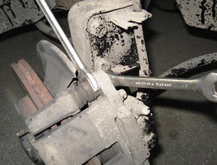 Снятие болта крепления цилиндра к верхнему направляющему пальцу суппорта Лада Гранта (ВАЗ 2190)