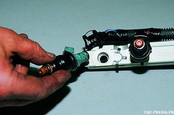 Покачивание форсунки из стороны в строну, и дальнейшее её извлечение из отверстия в топливной рампе