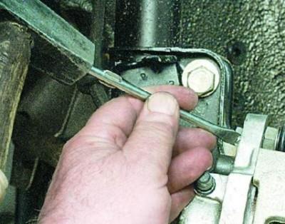 Отогните стопорящую шайбу, которая расположена на задней поверхности тормозного суппорта.