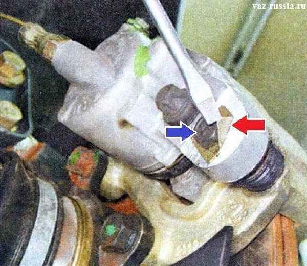 Отгибание стопорной шайбы и болт направляющего пальца крепления нижней части скобы тормозного суппорта
