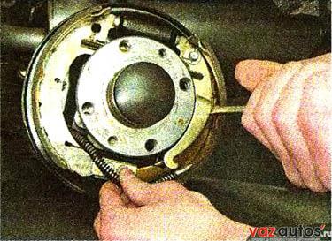 У тормозного механизма левого заднего колеса большой шлицевой отверткой сдвигаем распорный рычаг вперед и снимаем серьгу троса с крючка распорного рычага