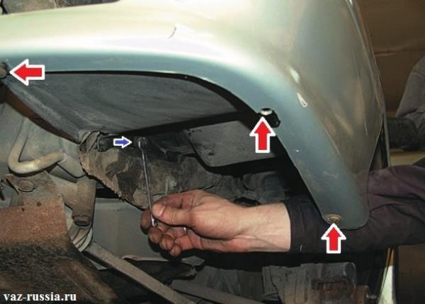 Красными стрелками указаны места где подкрылка винтами крепиться к крылу автомобиля, а синей стрелкой указан болт крепления подкрылки к нижней части брызговика
