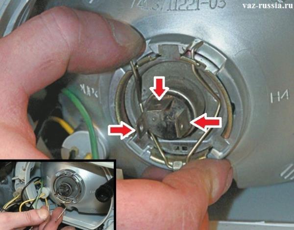 Отведение пружинного фиксатора в самый низ, чтобы он не мешал снятию лампы