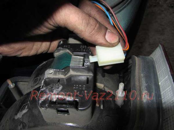 отсоединить штекер с проводами от заднего фонаря на ВАЗ 2110-2112