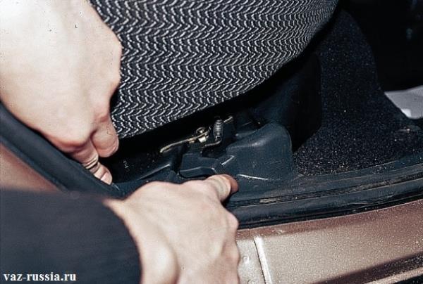 Отжимание защёлки крепления подушки заднего сиденья и её снятие