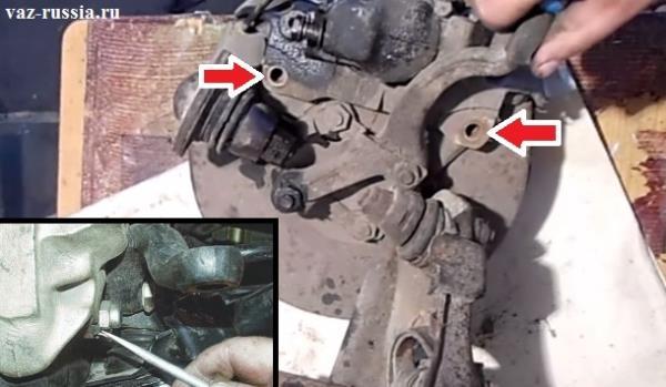 Стрелками указаны два болта которые крепят тормозной суппорт к поворотному кулаку, но чтобы данные болты вывернуть нужно будет с помощью бородка сперва отогнуть стопорные пластины которые не дают им отвернуться