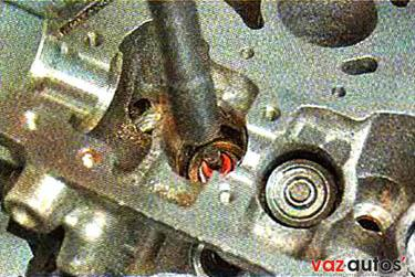 Легкими ударами молотка через оправку, напрессовываем колпачок на направляющую втулку клапана