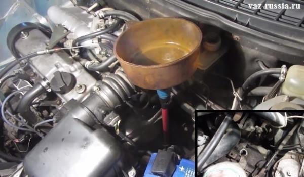 На маленьком фото изображена пробка заливного отверстия в коробке нового образца, а на основном фото показано как в это отверстие нужно заливать масло