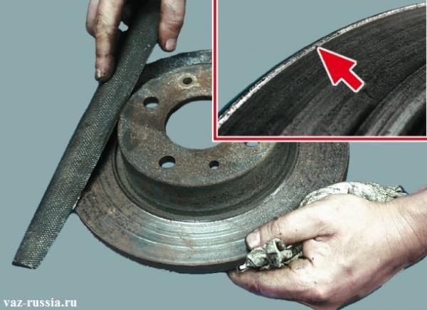 Удаление при помощи напильника буртика, который со временем образуется на диске и указан он ещё стрелкой на маленьком фото