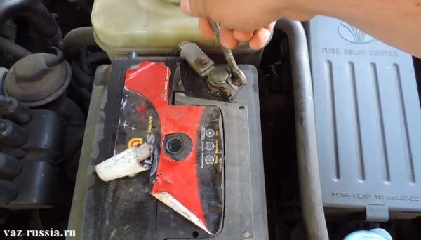 Ослабление гайки крепящей плюсовую клемму к выводу батареи