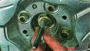 Постукивая по кернеру молотком, отгибаем замятый в проточки вала привода край гайки (в двух местах)