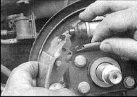 21. Установите переднюю колодку и зацепите пружину регулятора за штифт с тыльной