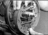 6. Осторожно подайте на себя и снимите колодки в сборе с регулятором и тросом