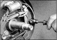 4. Снимите прижимные пружины колодок, для чего нажмите на колпачок и поверните