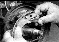 9. Отсоедините от передней колодки регулятор и пружину.