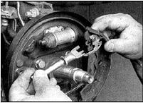 10. Отсоедините регулятор и пружину от задней колодки.